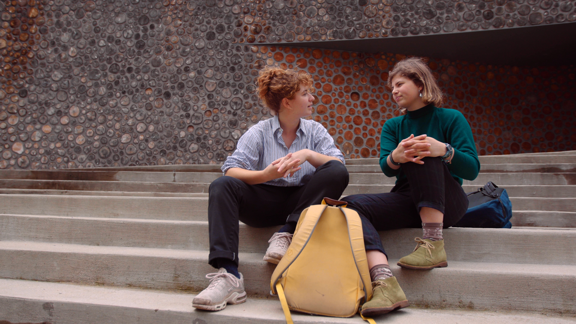 Two young college students sitting on stairs talking to each other.