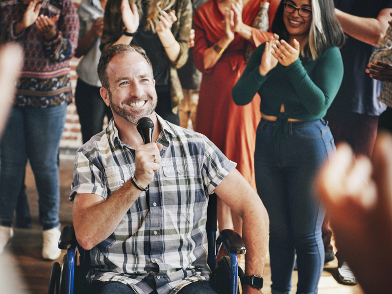 Middle aged man in a wheel chair on a microphone with people clapping in the background