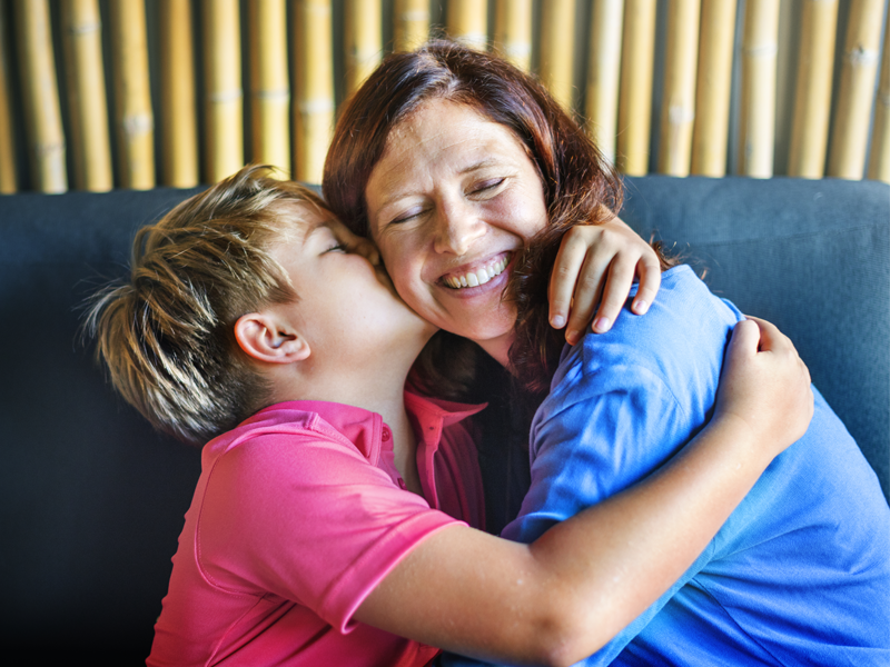 A young boy is giving his mother a hug and a kiss on the cheek.