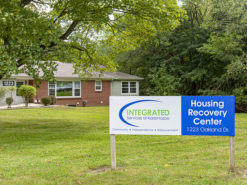 """A house in the background with a sign in front that has the ISK logo and reads """"Housing Recovery Center"""""""