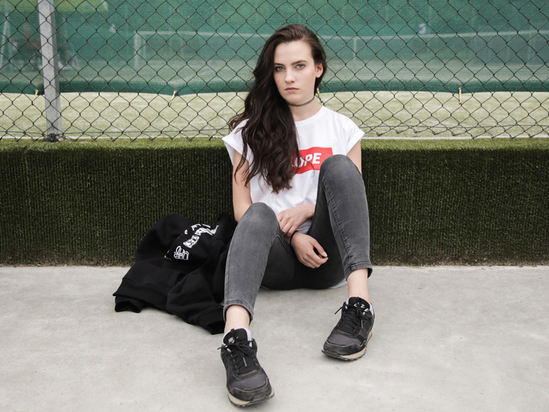 Teenage girl sitting in front of a school fence frowning at the camera