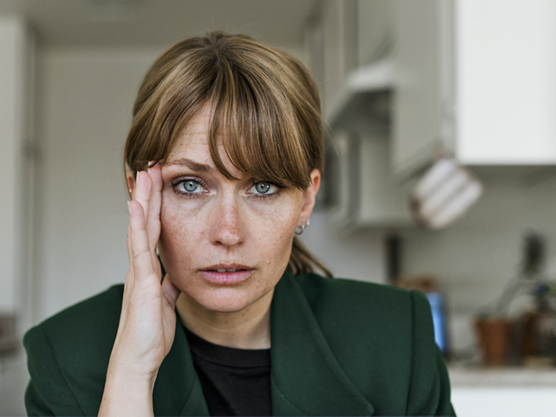 A woman in a green jacket looking directly into the camera with her hand on her temple looking stressed