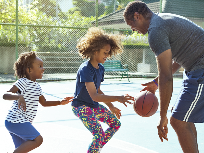 Two little girls and their father playing basketball together.