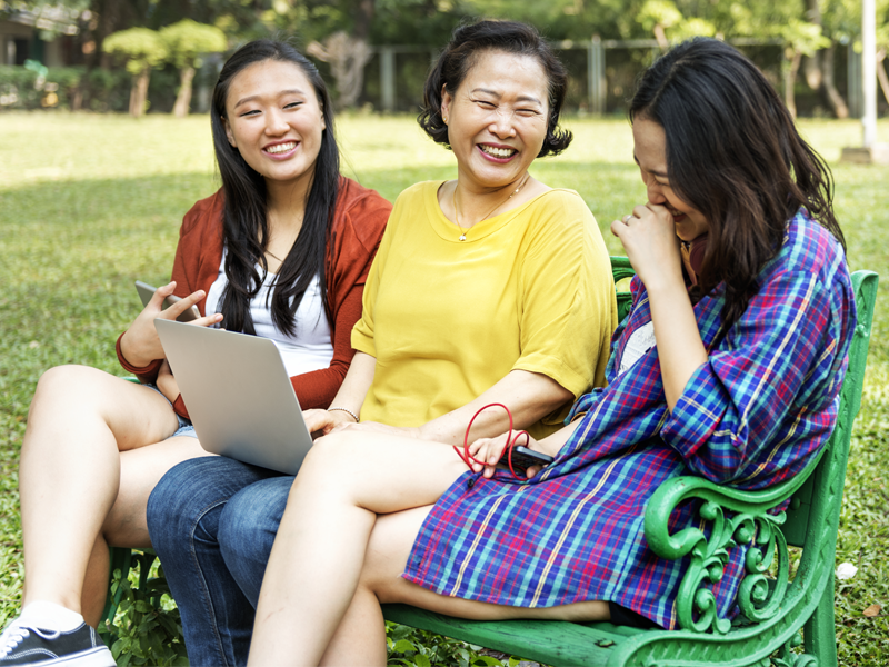 Three Asian women sitting on a park bench laughing together.