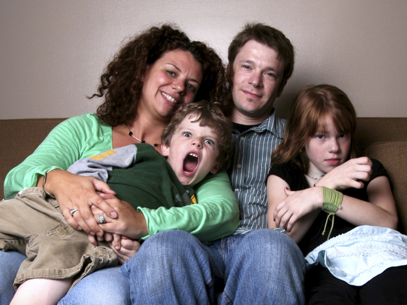 a mix couple sitting on a couch with their two children