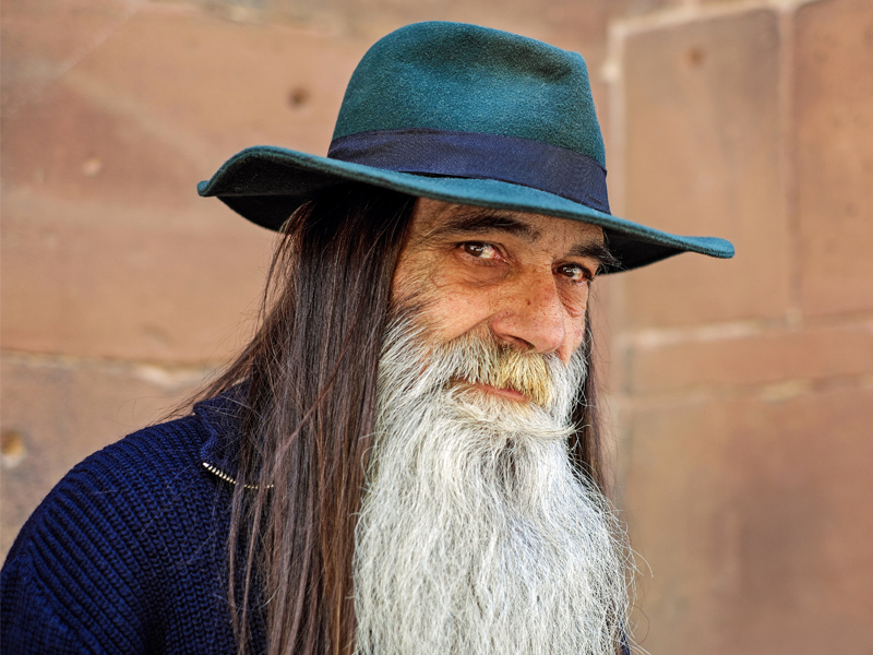 A man in his 50s or 60s with long hair and a really long white beard wearing a blue hat.