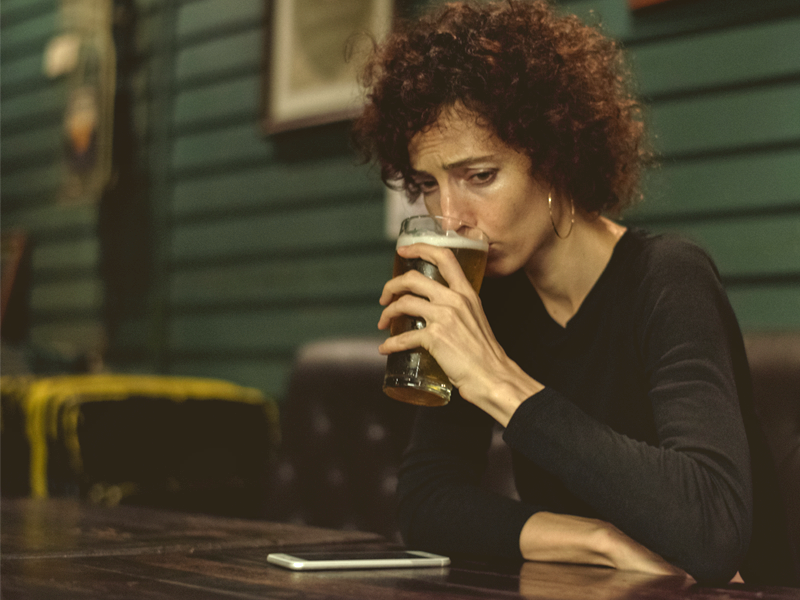 A woman in a dark room drinking a lone. Her cell phone is on the table.