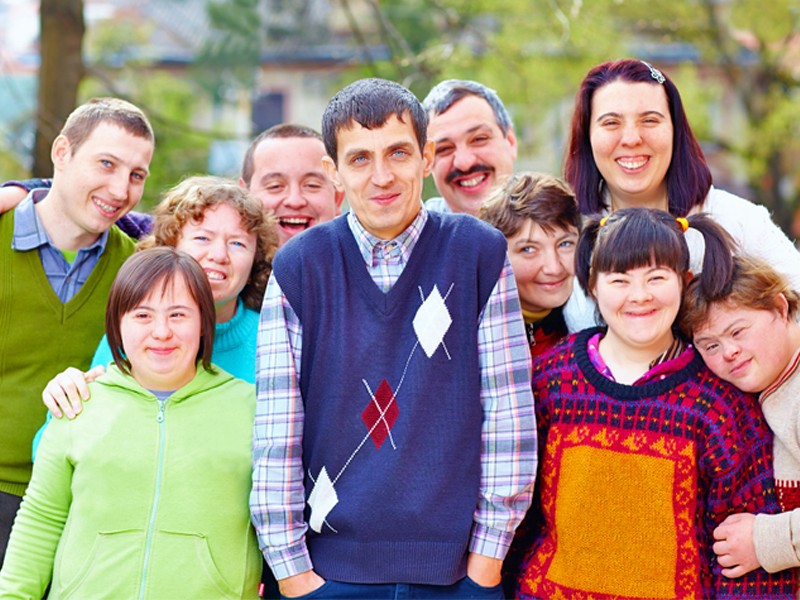 A large group of adults of different ages and different disabilities smiling at the camera.