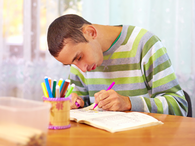 A young man with a developmental disabilities coloring in a book with markers.