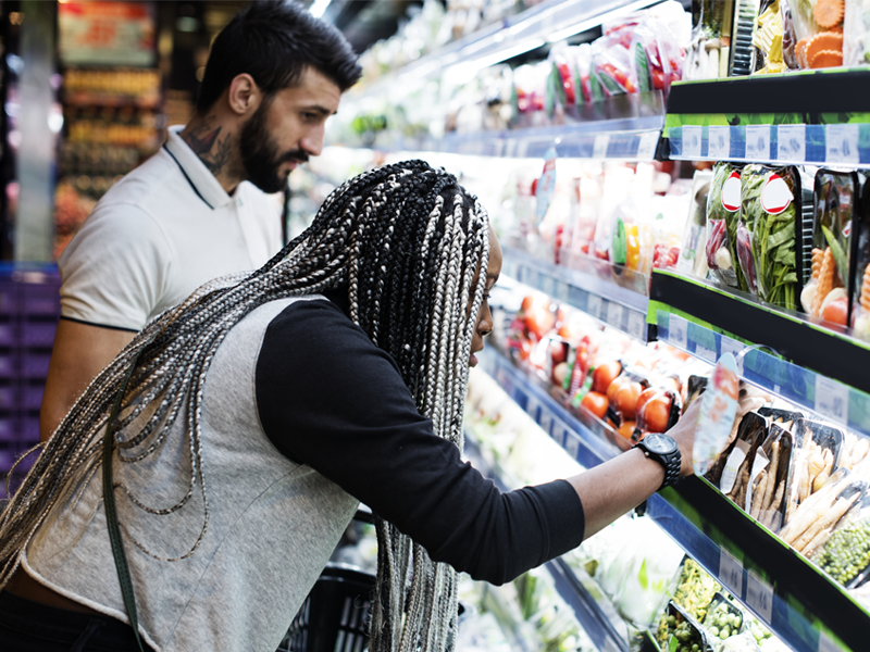 A woman and main shopping in a grocery store in the fresh food section.