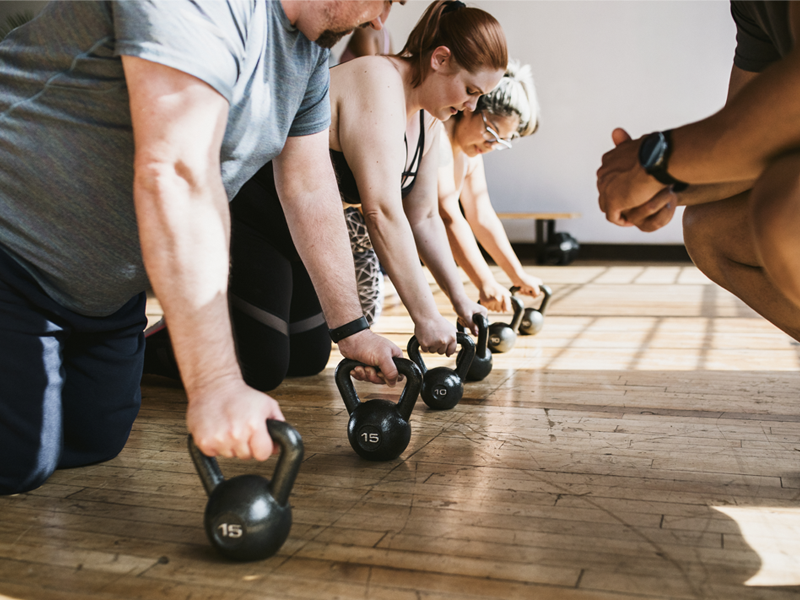 A group of people working out with kettle bells why a trainer watches