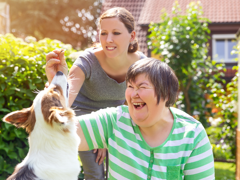 Two woman playing with a dog. One of the woman has a developmental disability