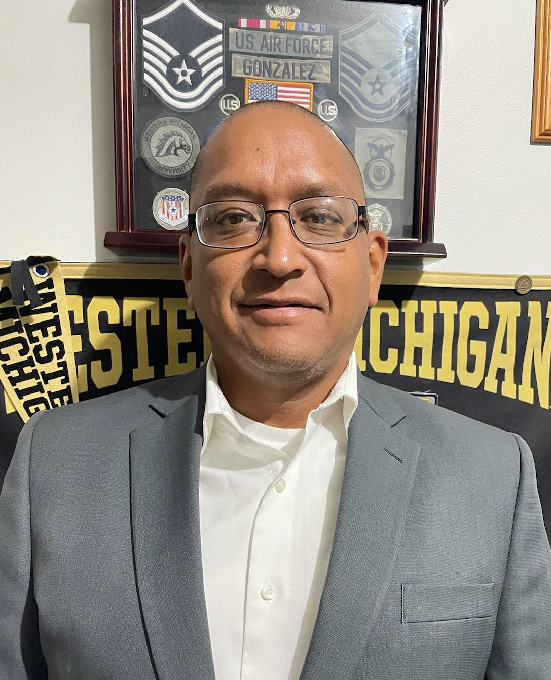"""Juan Gonzalez is the Veteran Navigator for Integrated Services of Kalamazoo standing by a wall with banners that read """"wester Michigan"""" and military metals."""