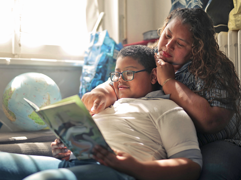 A mother and son sit together in a bedroom as the son reads from a book.