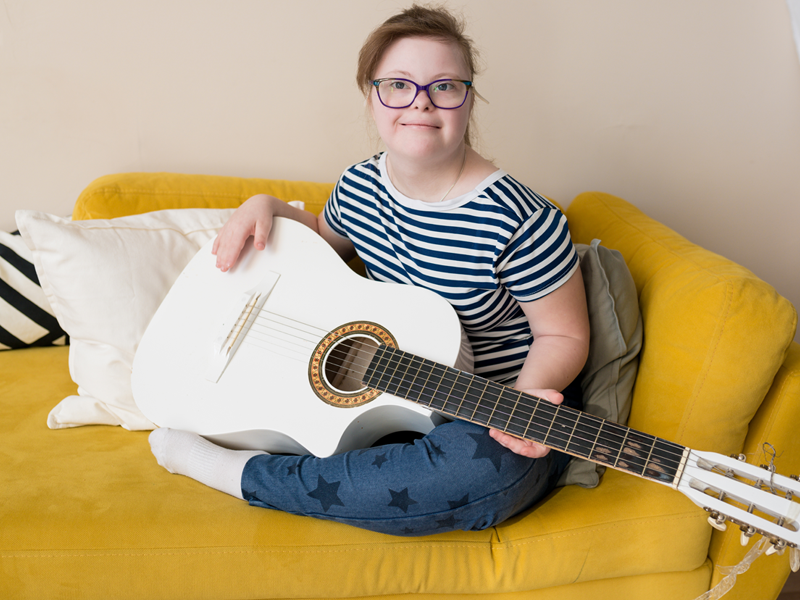 A teenage girl with down syndrome sitting on a yellow couch playing a white guitar.