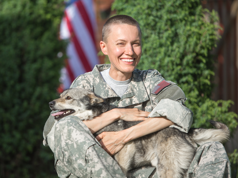 A woman wearing military camo is sitting on the ground holding a service dog. In the background is the United States flag.