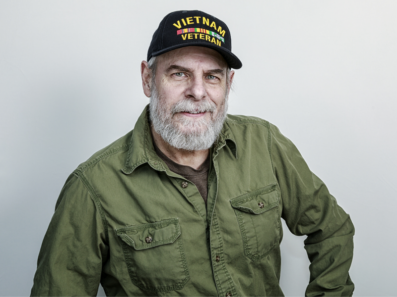 A photo of a older man wearing a hat that say Vietnam veteran with a white beard wearing a army green.