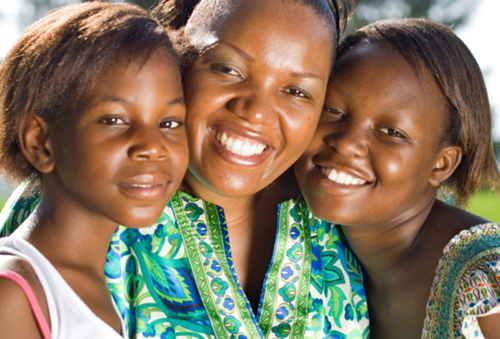 A mother with her two teenager daughters smiling at the camera.