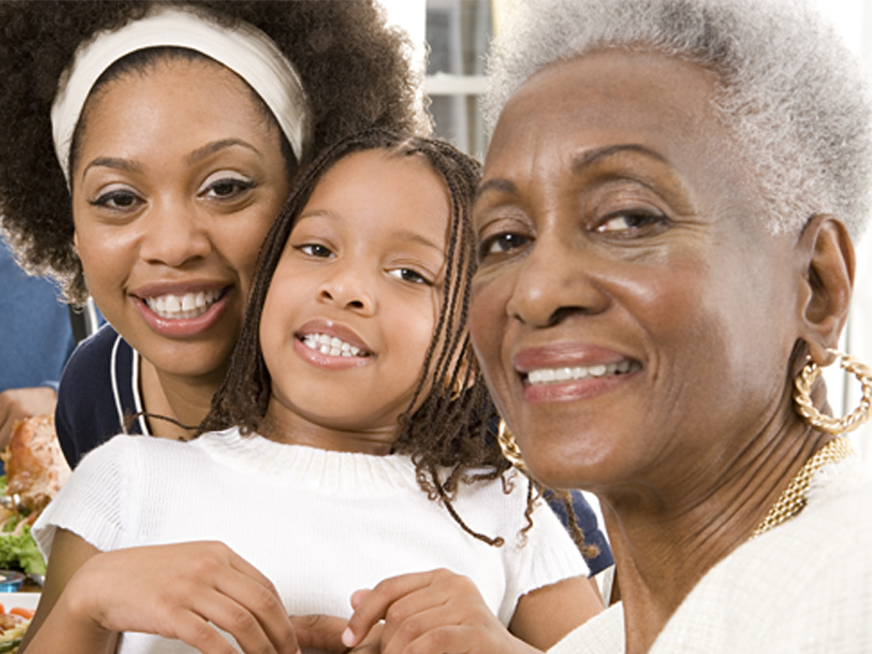 An image of a generational family. A mother, daughter and grandmother all smiling at the camera.
