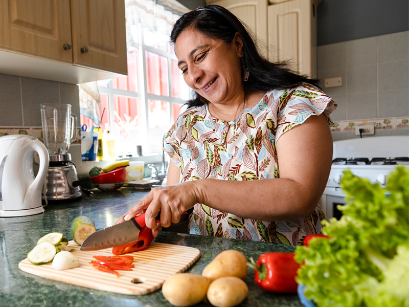 A woman at her kitchen counter cutting red peppers and cucumbers.