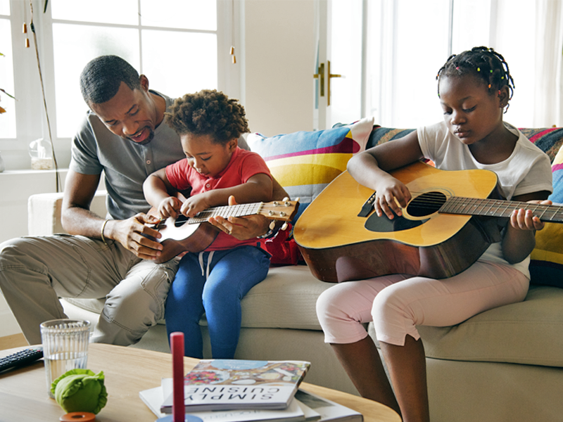 A father sitting on a couch teaching his young son and daughter how to play guitar.